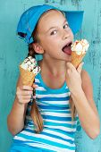 Portrait of 7 years old kid girl eating tasty ice cream on blue background