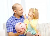 family, children, money, investmen and happy people concept - happy father and daughter with big pin