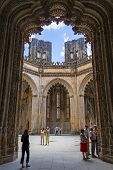Batalha, Portugal - July 17, 2013: Tourists stroll around the interior of the Unfinished Chapels - C