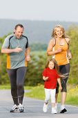 Family jogging for sport for fitness outdoors with the kids