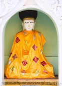 stock photo of yangon  - Buddha image with an orange robe at the Shwedagon Pagoda in Yangon the capital of Republic of the Union of Myanmar - JPG