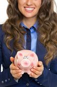 Closeup On Smiling Business Woman Showing Piggy Bank