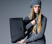 fashion model in modern clothes holding handbag posing on gray background