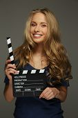 Young woman with long hair and blue eyes holding cinema clapper board