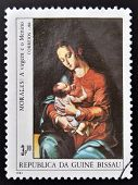A stamp printed in Republic of Guinea Bissau shows draw by artist Morales - Virgin and child