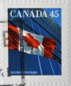 stamp printed in Canada shows image of a the Canadian flag and a modern building