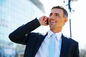 image of people talking phone  - Portrait of a smiling businessman talking on the phone at street - JPG