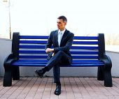 Portrait of a businessman sitting on bench