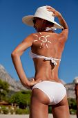 picture of sun tan lotion  - Tanning lotion in the shape of sun on woman - JPG