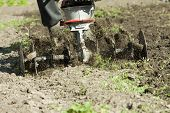 image of plowing  - Man working the field in the spring with a plow machine - JPG