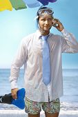 Young businessman using seashell as mobilephone on the beach wearing shirt and tie and scuba diving