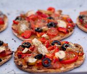 foto of pesto sauce  - Home baked vegan mini pizza with olives red pepper tomato pear oregano and pesto on parchment paper - JPG