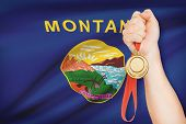 Medal In Hand With Flag On Background - State Of Montana. Part Of A Series.