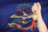 Medal In Hand With Flag On Background - State Of North Dakota. Part Of A Series.