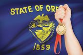Medal In Hand With Flag On Background - State Of Oregon. Part Of A Series.