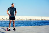 Muscular male athlete taking break standing relaxed outdoors