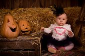 Little Baby Girl On Halloween Party With Pumpkin