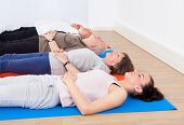 Trainer And Senior People Lying On Exercise Mats