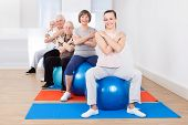 Trainer And Senior Customers Sitting On Fitness Balls