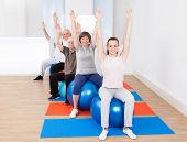 Trainer And Senior Customers Stretching On Fitness Balls