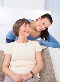 Portrait Of Happy Caregiver With Senior Woman