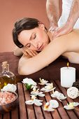 Woman Receiving Back Massaging In Spa