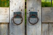 Wooden Gate With Rusty Old Iron Knockers