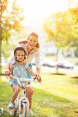 Portrait Of Happy Mother Helping Baby Girl Riding Bicycle In Par