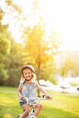Portrait Of Happy Baby Girl Riding Bicycle Outdoors