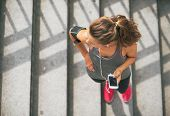 Portrait Of Fitness Young Woman With Cell Phone Outdoors In The