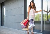 Happy Young Woman With Shopping Bags Entering Shop