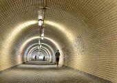 people walking in a long tunnel