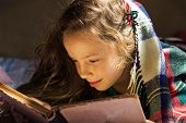 portrait of cute curly school girl reading an old book at cold day