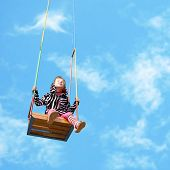 image of rapture  - happy little girl on a swing on sky background - JPG