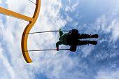 Silhouette Of A Boy Swinging On A Swing