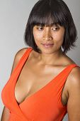 picture of cleavage  - Young asian woman wearing a low cut orange dress showing cleavage - JPG