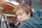 Cool Teenager Boy Is Leaning Against A Motorcycle