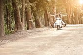 Young attractive couple traveling along road on scooter
