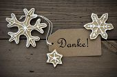 stock photo of ginger bread  - The German Word Danke which means Thanks on a Label with Ginger Bread Snowflakes with white Decoration on Wooden Background - JPG