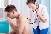picture of auscultation  - Horizontal view of coughing man having examination - JPG