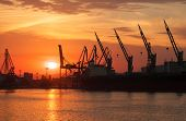Silhouettes Of Cranes And Cargo Ships In Varna Port At Sunset