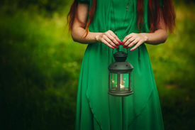 picture of fairy  - Woman with long red hair holding lantern with burning candle in forest - JPG