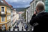 Young girl is taking picture with her phone in the old part of Bergen, Norway