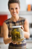 Closeup On Happy Young Housewife Showing Jar Of Pickled Cucumber
