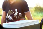 stock photo of clubbing  - Close up of professional golf gear on the golf course at sunset - JPG