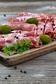 Постер, плакат: Various Meats On Serving Board With Rustic Background