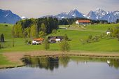 foto of farm landscape  - landscape in Bavaria at alps mountains with farm houses and lake - JPG