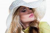 Beautiful blond girl in a hat enjoying the sun on the beach