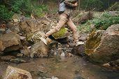 Female Hiker Crossing A Creek