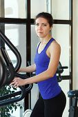 picture of elliptical  - Young woman doing exercises with elliptical trainer in gym - JPG